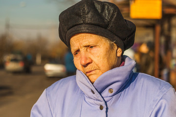 portrait of sad old woman in the city