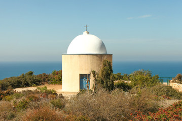 Traditional Greek church with dome and the sea in the background