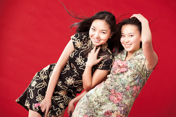 Two cheerful girl-friends. Red background