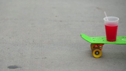 A Skateboard Passing By With Two Drinks On Top