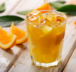 Orange juice in glass with  fresh fruits on a wooden background