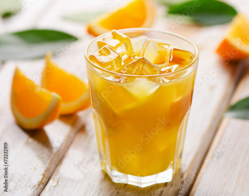 canvas print picture Orange juice in glass with  fresh fruits on  wooden background