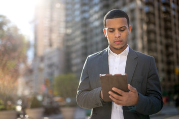 Young African American black Latino man using tablet pc