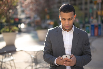 Young African American black Latino man texting cellphone