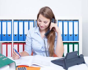 Frau mit langen blonden Haaren nimmt am Telefon Bestellung auf