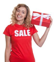 Lachende Frau im Sale-Shirt lauscht an Geschenk