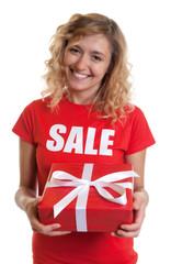 Lachende blonde Frau im Sale-Shirt mit Geschenk