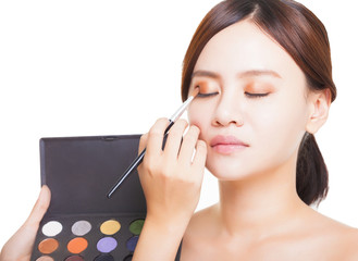 Makeup artist applying colorful eyeshadow on model's eye with a