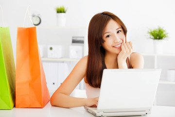 happy young asian woman using a laptop with bags.