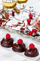 chocolate cake decorated with raspberries in white plate