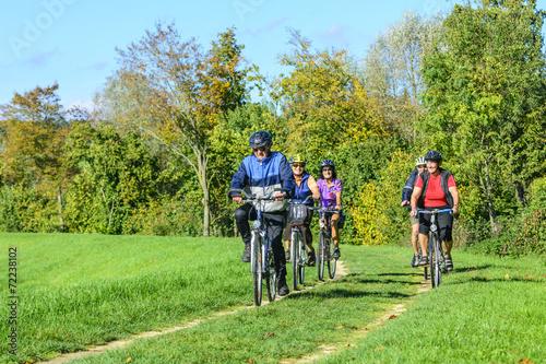 Leinwanddruck Bild Senioren-Gruppe mit dem Rad unterwegs