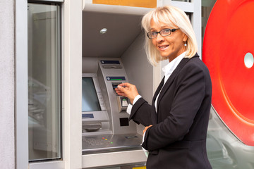 Bussines woman taking money from ATM