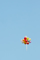 A bunch of painted balloons in a blue sky flying away