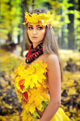 Portrait of a beautiful girl in a wreath of autumn leaves