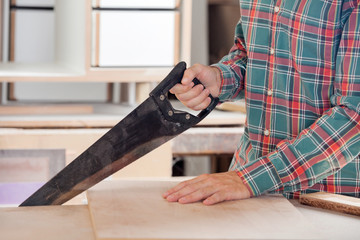 Carpenter Cutting Wood With Handsaw