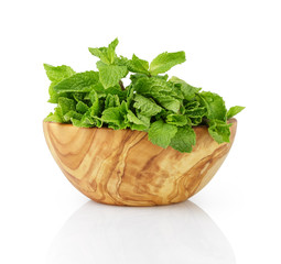 bunch of fresh mint in wood bowl