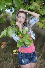 Beautiful girl wearing denim jacket in a forest