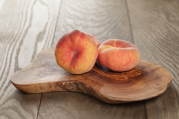 ripe flat peaches on olive board
