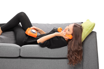 Girl lying on a sofa and talking on vintage phone