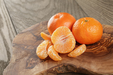 ripe tangerines on olive board