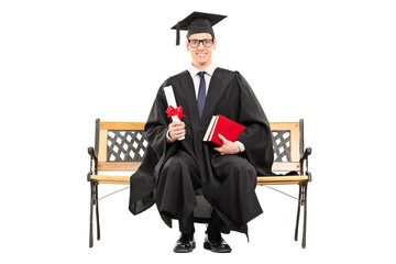 Delighted college graduate sitting on a bench