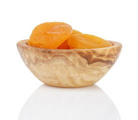 heap of dried apricots in wood bowl