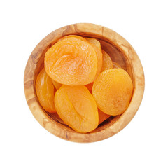heap of dried apricots in wood bowl from above