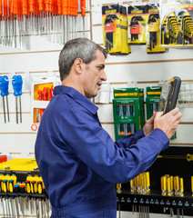 Worker Looking At Packed Product In Hardware Store