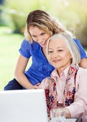 Senior Woman And Granddaughter Using Laptop At Porch