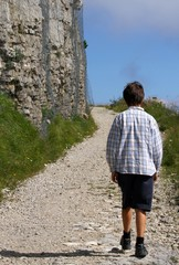 lonely child walks on the mountain path next to the huge wall of