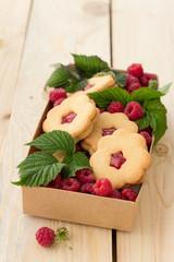 Homemade cookies with raspberry jam and fresh raspberries