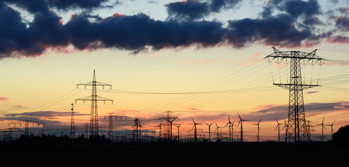 Windräder und Strommasten im Abendlicht