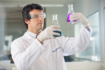 Researcher Examining Flasks With Different Samples