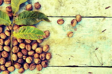 Walnuts with green leaves on wooden background
