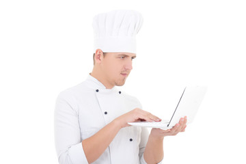young man in chef uniform with laptop isolated on white