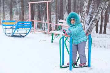 Happy kid girl child outdoors in winter playing and training
