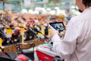 Man choosing lawnmowers in supermarket or DIY