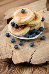 Homemade fritters with blueberries over rustic wooden background