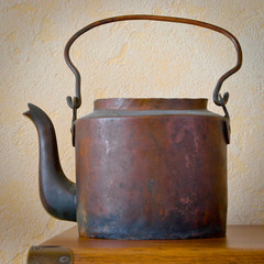 Old copper tea-pot on a table