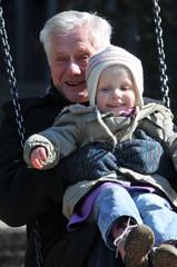 Großvater mit Engeltochter auf dem Spielplatz