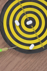 White pills on yellow and black dart target