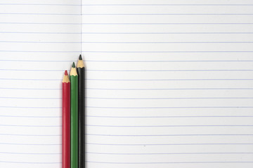 Student empty notebook with set of colorful pencil on top