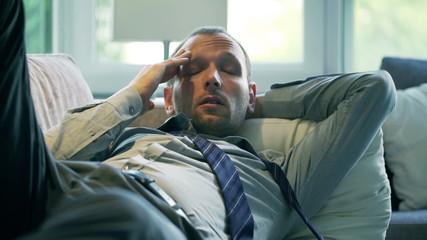 Businessman having headache and lying on the sofa, steadycam