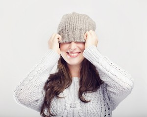 playful cute winter girl covers eyes with hat