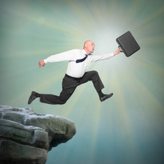 Senior businessman jumping from a edge of cliff.