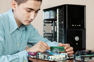 Technician repairing computer hardware in the lab. Studio shot.
