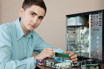 Technician repairing computer hardware in the lab, looking at th