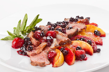 Slices of fried meat on a plate with fruit and berries.
