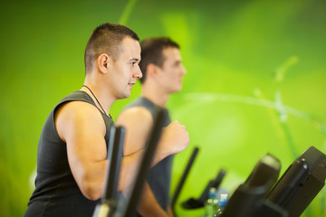 Young man jogging on treadmill in the gym