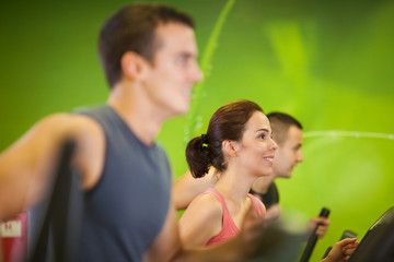 Smiling woman and two men working out at the gym